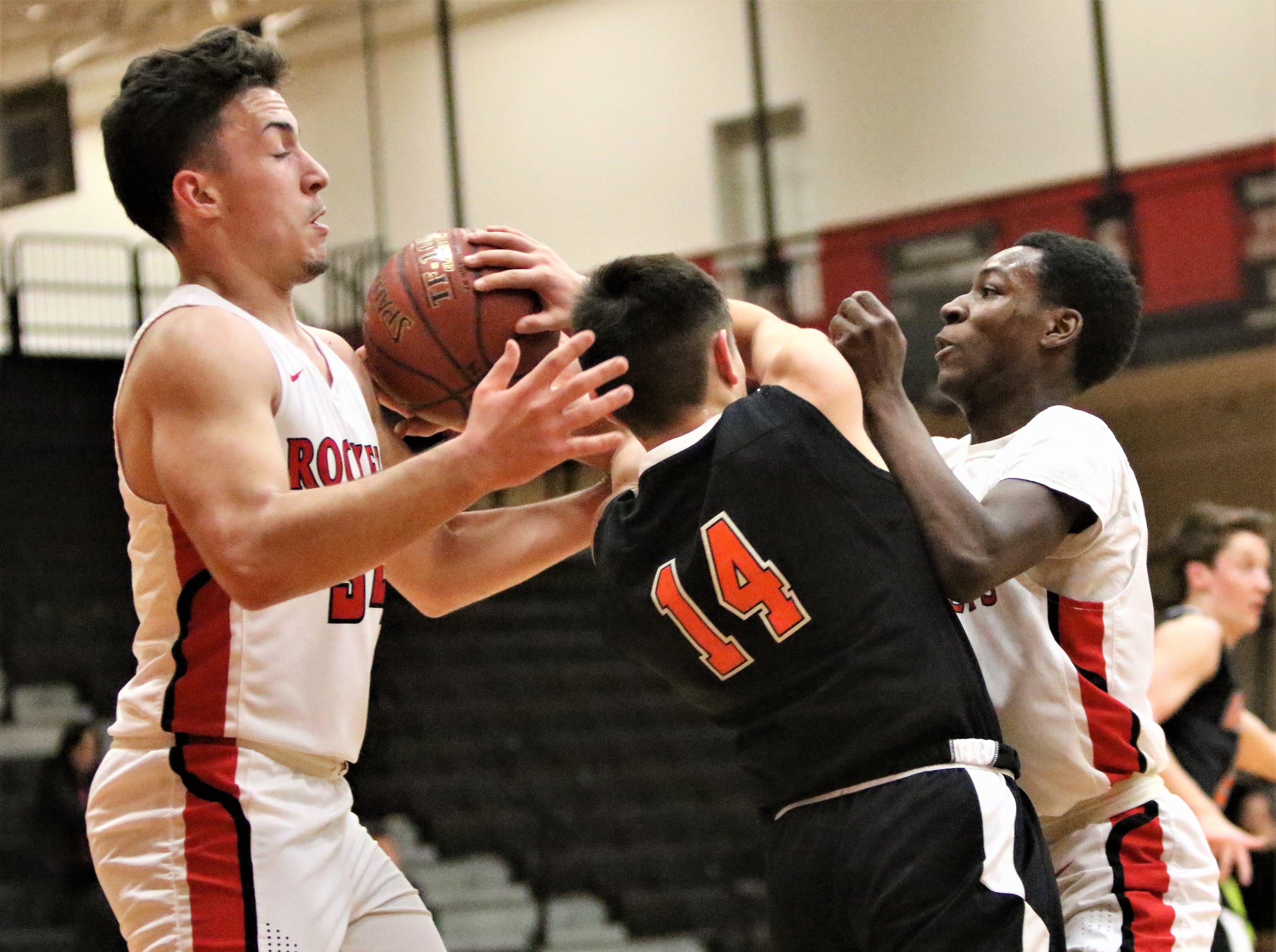 Grafton guard Tyler Tsui (14) fights through a double team from South Milwaukee after pulling down a rebound during a game on Jan. 22, 2019.