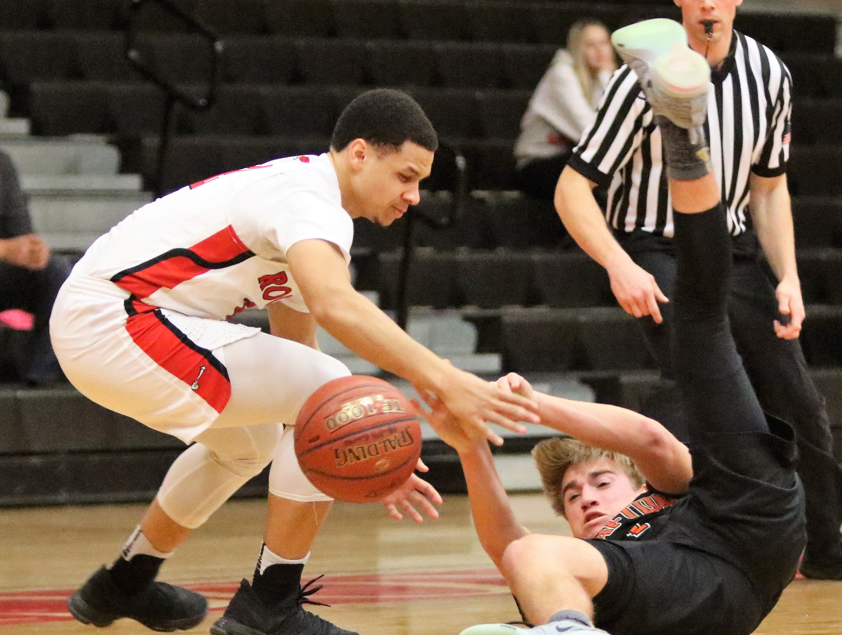 South Milwaukee forward Dez Fitzpatrick battles for a loose ball with Grafton guard Brady Ward during a game on Jan. 22, 2019.