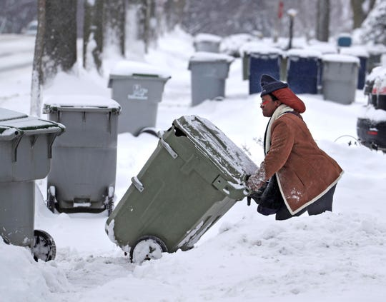 Residents brave several inches of snow to place their trash containers by the street near North 60th and West Clarke streets in Milwaukee following  a winter storm.