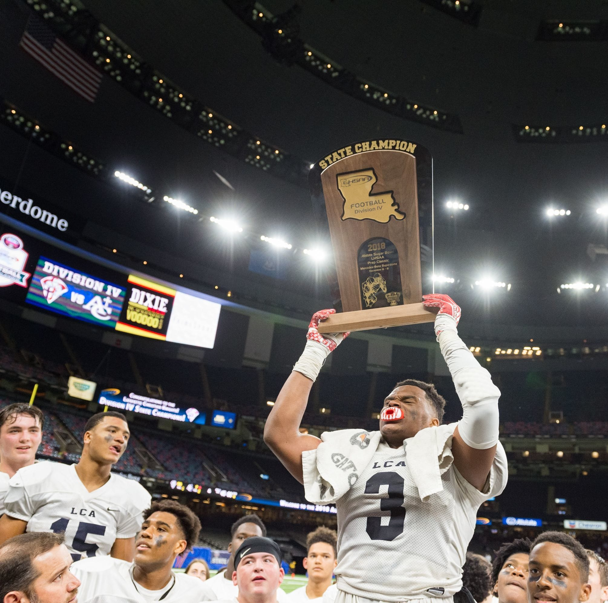 Lafayette Christian senior linebacker Martin Lee raises the Division IV state championship trophy on Dec. 6.  SCOTT CLAUSE/USA TODAY Network Lafayette Christian senior linebacker Martin Lee raises the Division IV state championship trophy after LCA beat Ascension Catholic 56-7 in the Mercedes-Benz Superdome on Dec. 6.
