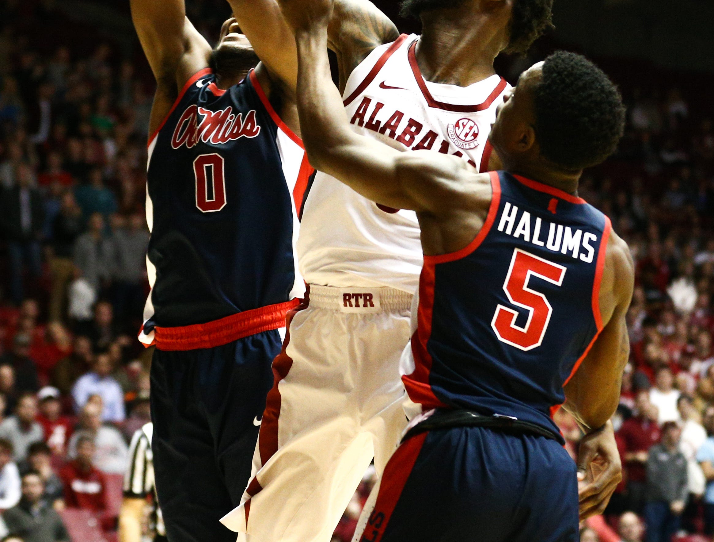 Jan 22, 2019; Tuscaloosa, AL, USA; Alabama Crimson Tide forward Donta Hall (middle) jumps for a rebound against Mississippi Rebels guard Blake Hinson (0) during the second half at Coleman Coliseum. Mandatory Credit: Marvin Gentry-USA TODAY Sports