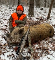 Easton Hall, a third grader at Madison Creek Elementary School, kneels next to the 350-pound wild hog he killed in Crossville.