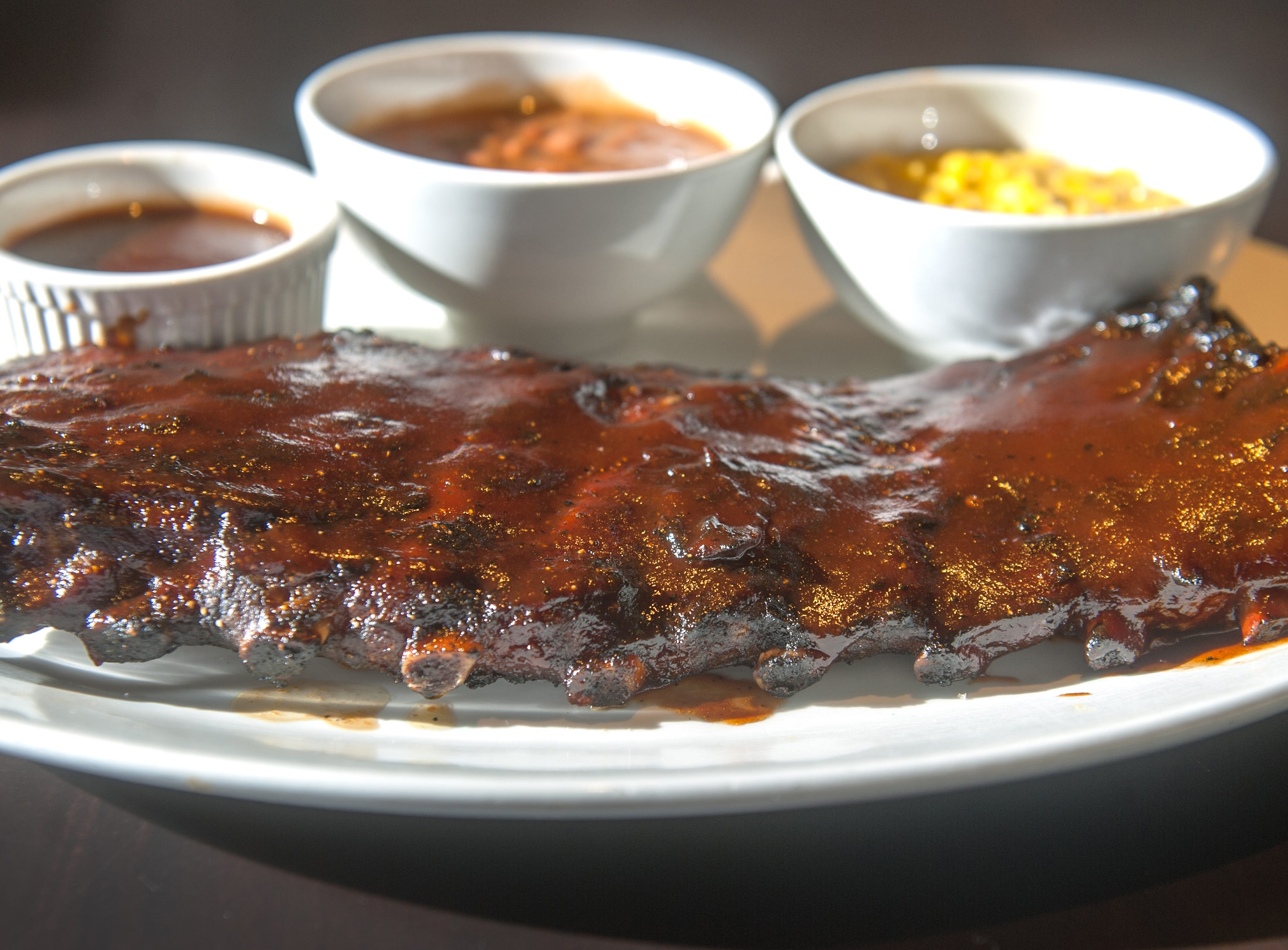 A full rack of St. Louis-style pork spare ribs with spicy barbecue sauce, creamed corn and barbecue pinto beans at Yard House.