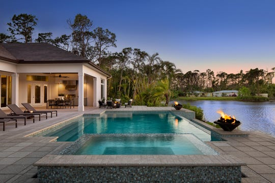 The pool of Divco Custom Homes' Baywood model, has fire features and overlooks a lake.