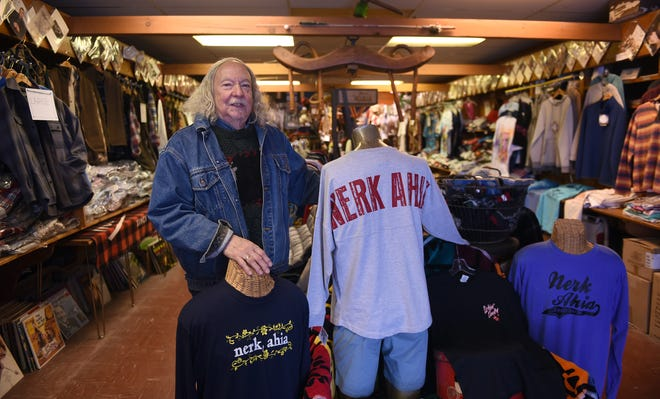 """Robin Pierce, owner of Cornell Clothing Company in downtown Newark, with a display of """"Nerk, Ahia"""" T-shirts. The local clothing retailer tries to offer harder to find or specialty items."""