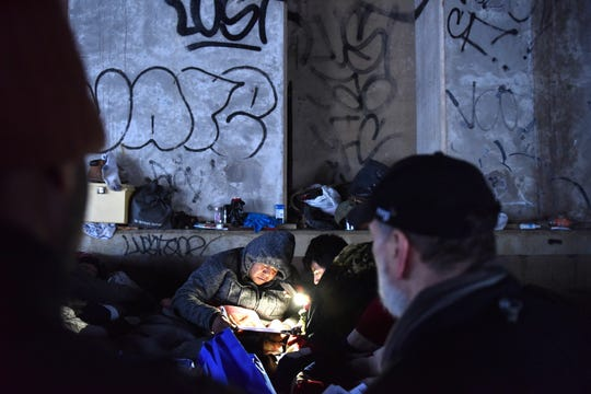 A homeless man fills out a survey after being woken up by volunteers conducting a homeless count in Palisades Park, on Wednesday January 23, 2019. A group of five men were sleeping under a Route 46 bridge.