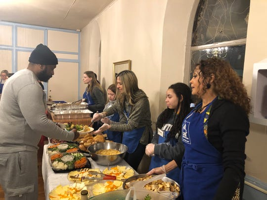 "Montclair councilwoman Renee Baskerville, foreground, was among the volunteers serving at the ""Shutdown Social"" for federal workers at Toni's Kitchen in Montclair on Tuesday, January 22."