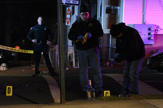 Members of the Paterson Police Department, including crime scene investigators, process the scene of a shooting at the intersection of N 10 St. and Temple St. at around 6:30 pm on Tuesday, January 22, 2019. Investigators pick up bullet casings marked by yellow lettered placards at the scene.