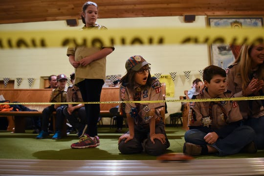 The Morris County Pinewood Derby at Holy Trinity Lutheran Church in Rockaway on Friday January 18, 2019. (Left, standing) Brenna Johnson, 11 and (left kneeling) Anika Zoeller, 10, both in Cub Scout pack 165 Arrow of Light den, watch as the cars race to the finish line.