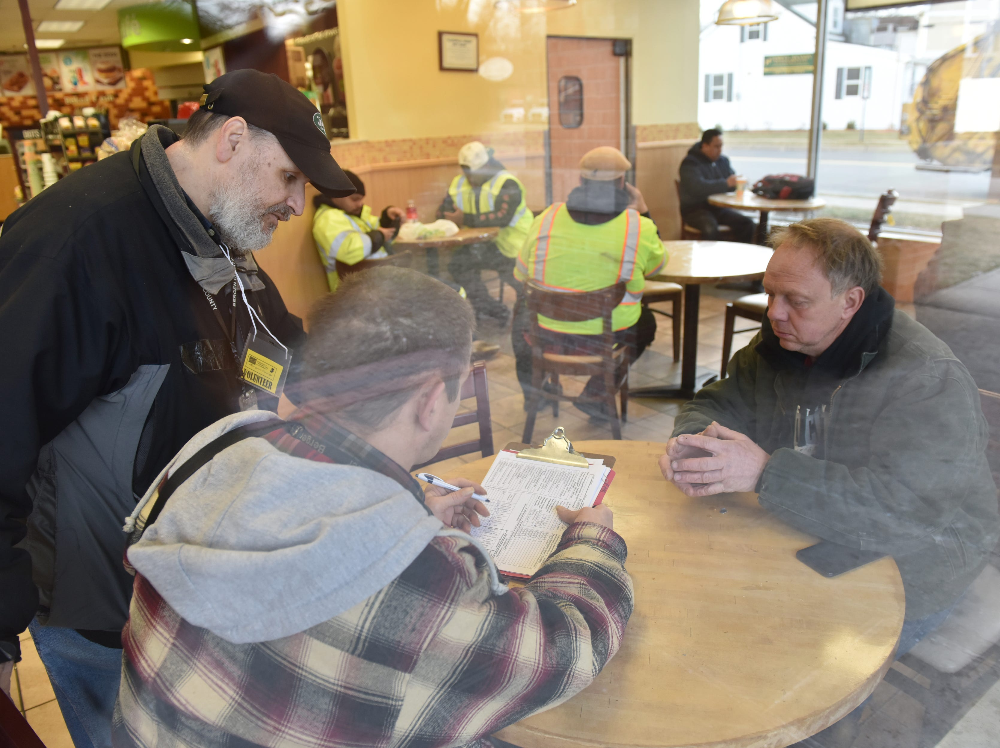 From left, Rocco Mazza, of Bergen County Human Services Center, and Paul Nickels, a volunteer, conduct a survey of Glenn Couzzo in Hackensack, at a QuickChek on Wednesday January 23, 2019. Couzzo and a friend slept in his car at the QuickChek parking lot.