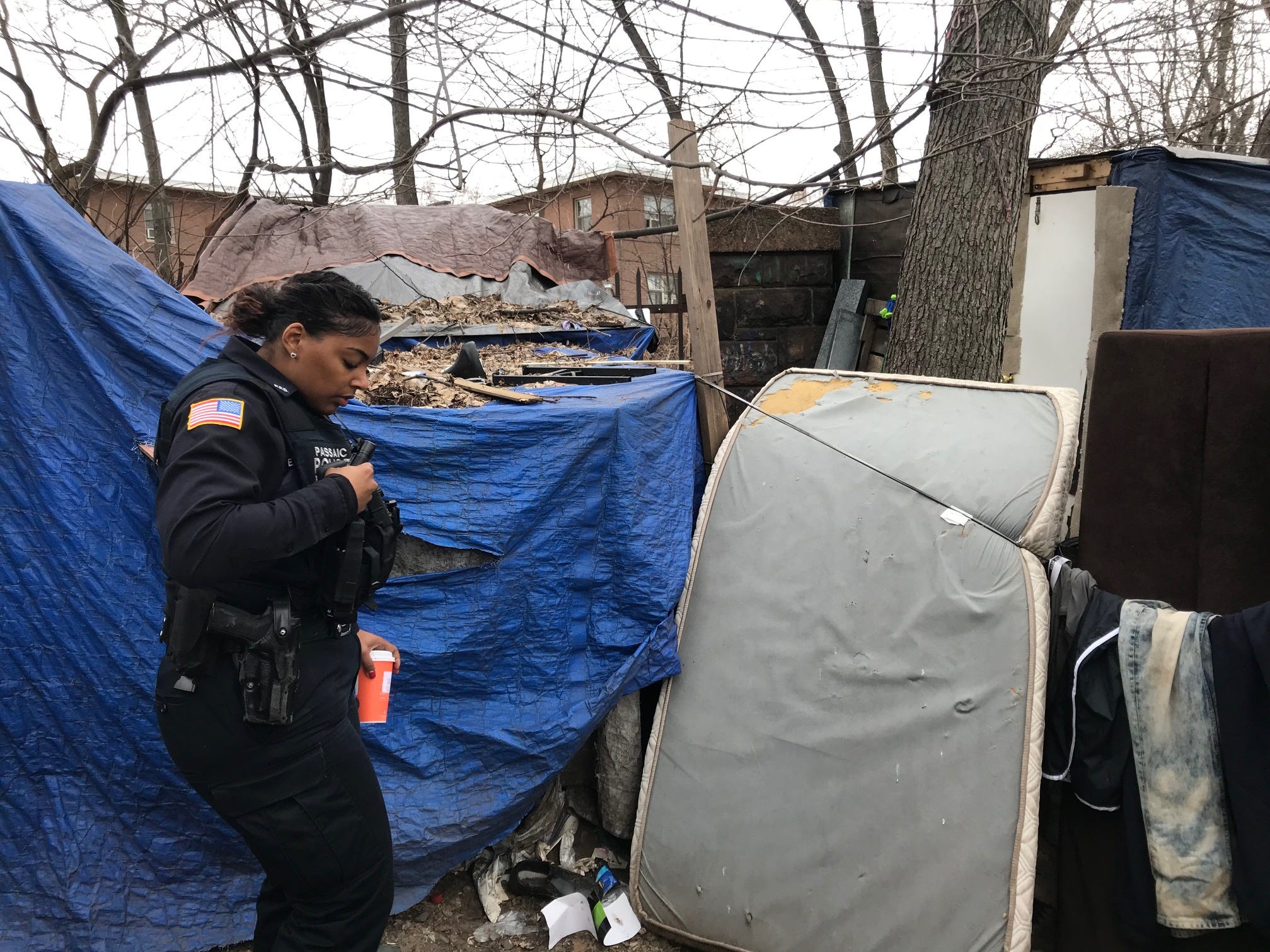 Passaic police officer helps with the annual Point in Time homeless headcount by checking on various lean-tos to see anyone's home. This encampment is in Dundee Island Park by the Passaic River.