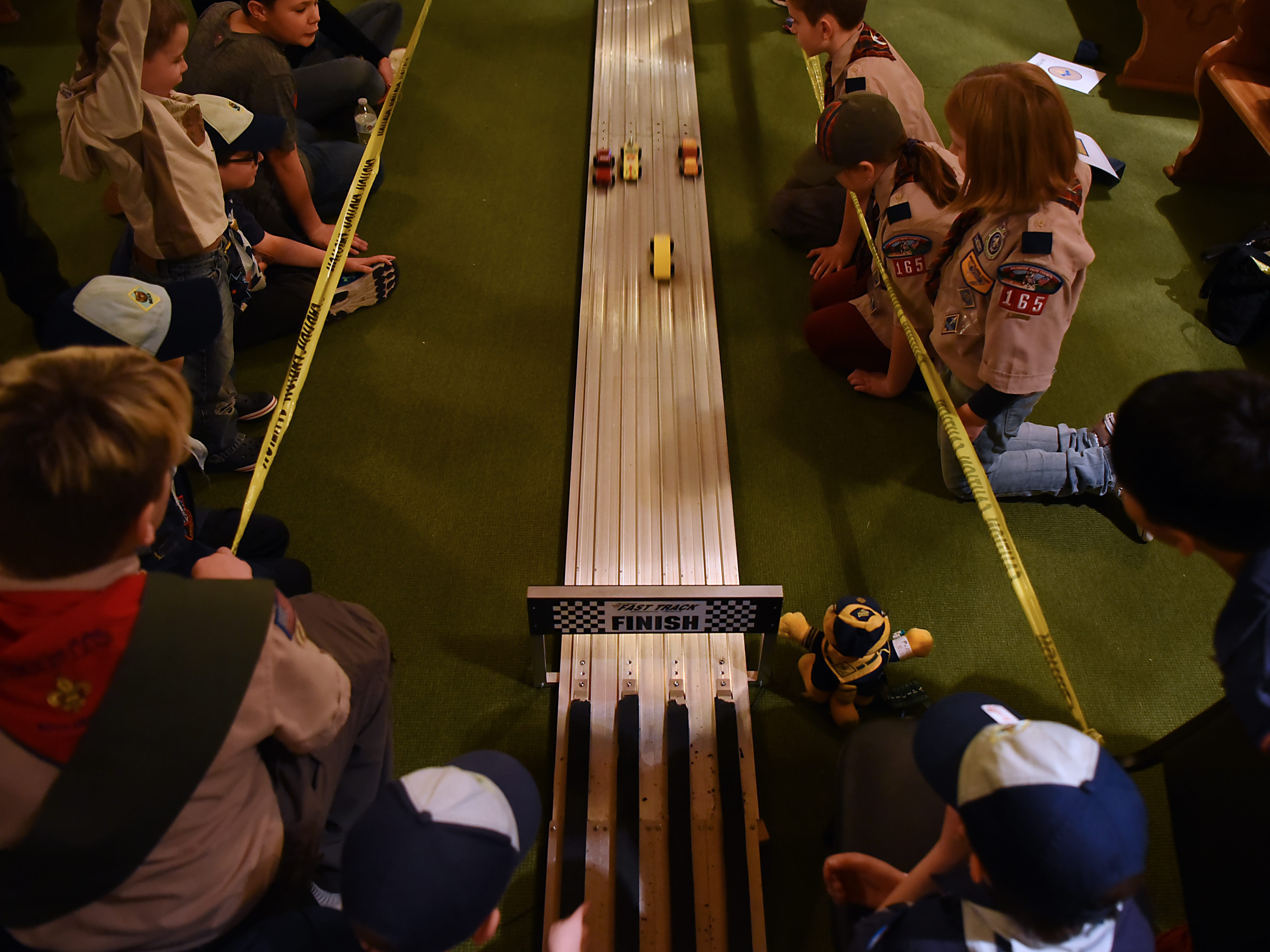 Cub Scouts watch the cars race to the finish line during the Morris County Pinewood Derby at Holy Trinity Lutheran Church in Rockaway on Friday January 18, 2019.