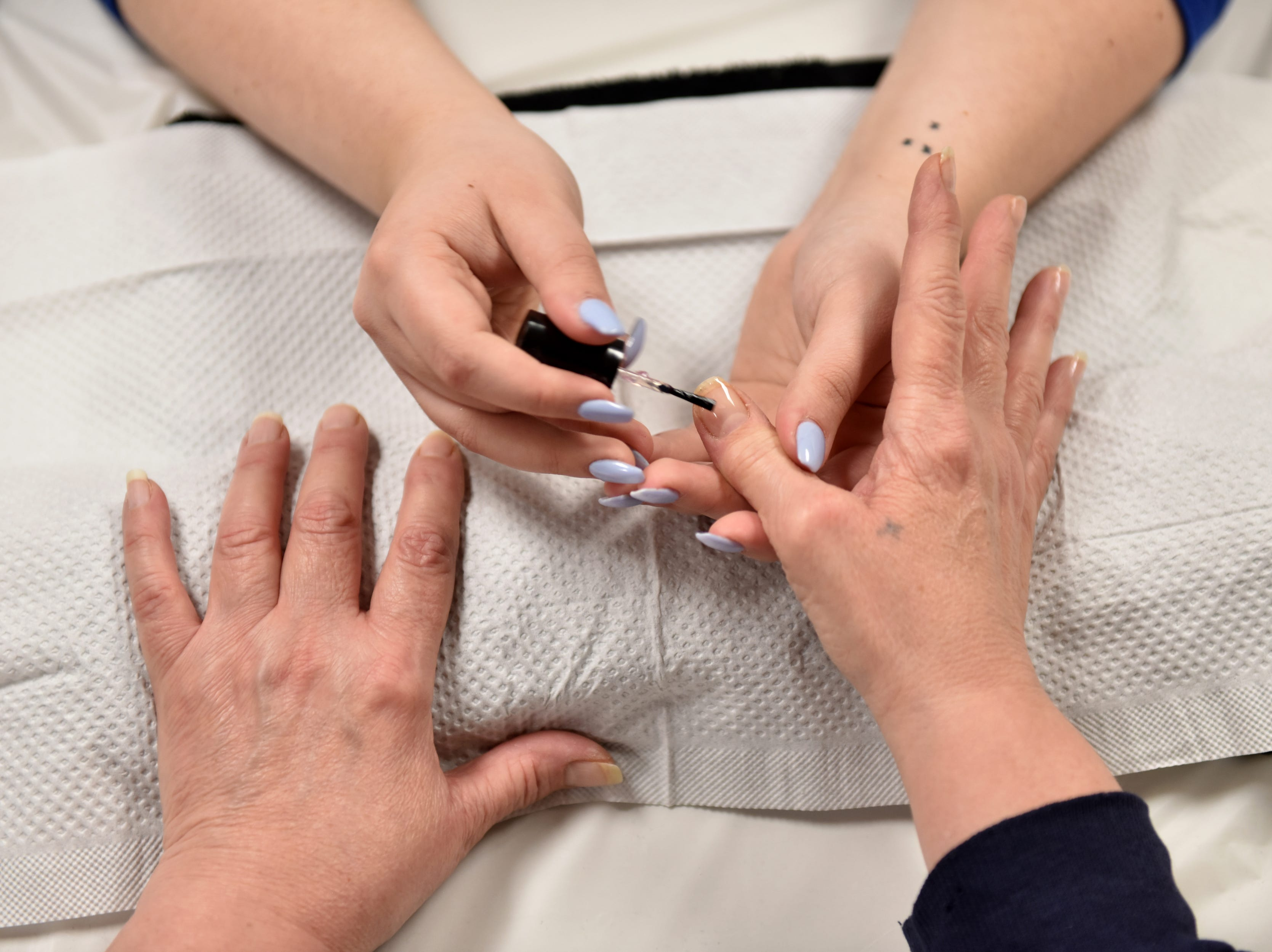 A woman receives a manicure that was given to her by a student of the Parisian Beauty Academy at the Bergen County Human Services Center in Hackensack, on Wednesday January 23, 2019.