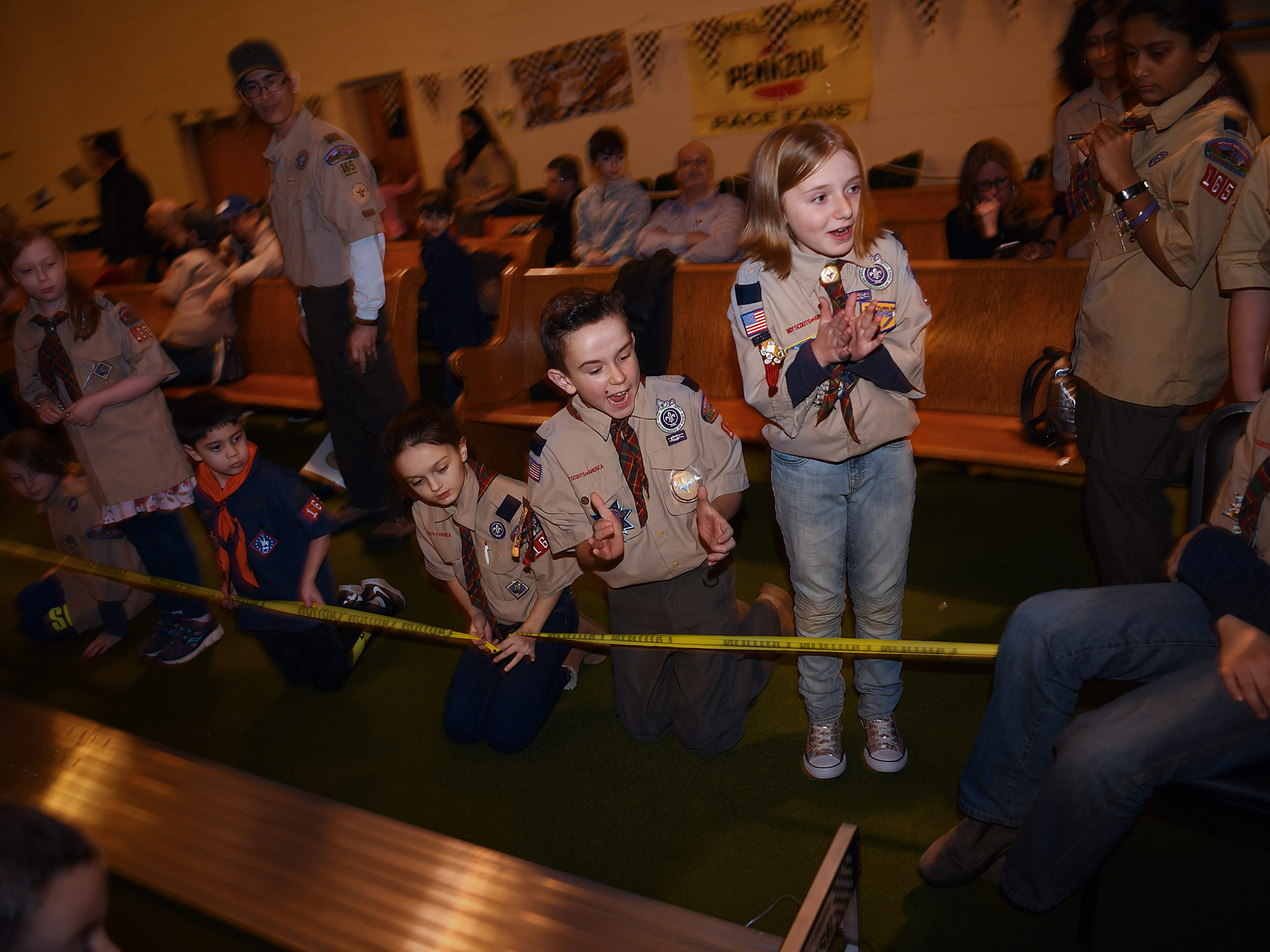 The Morris County Pinewood Derby at Holy Trinity Lutheran Church in Rockaway on Friday January 18, 2019. (Standing, right) Madison Sipple, 10 years old with Cub Scout pack 165 Arrow of Light den, claps as the cars race to the finish line.