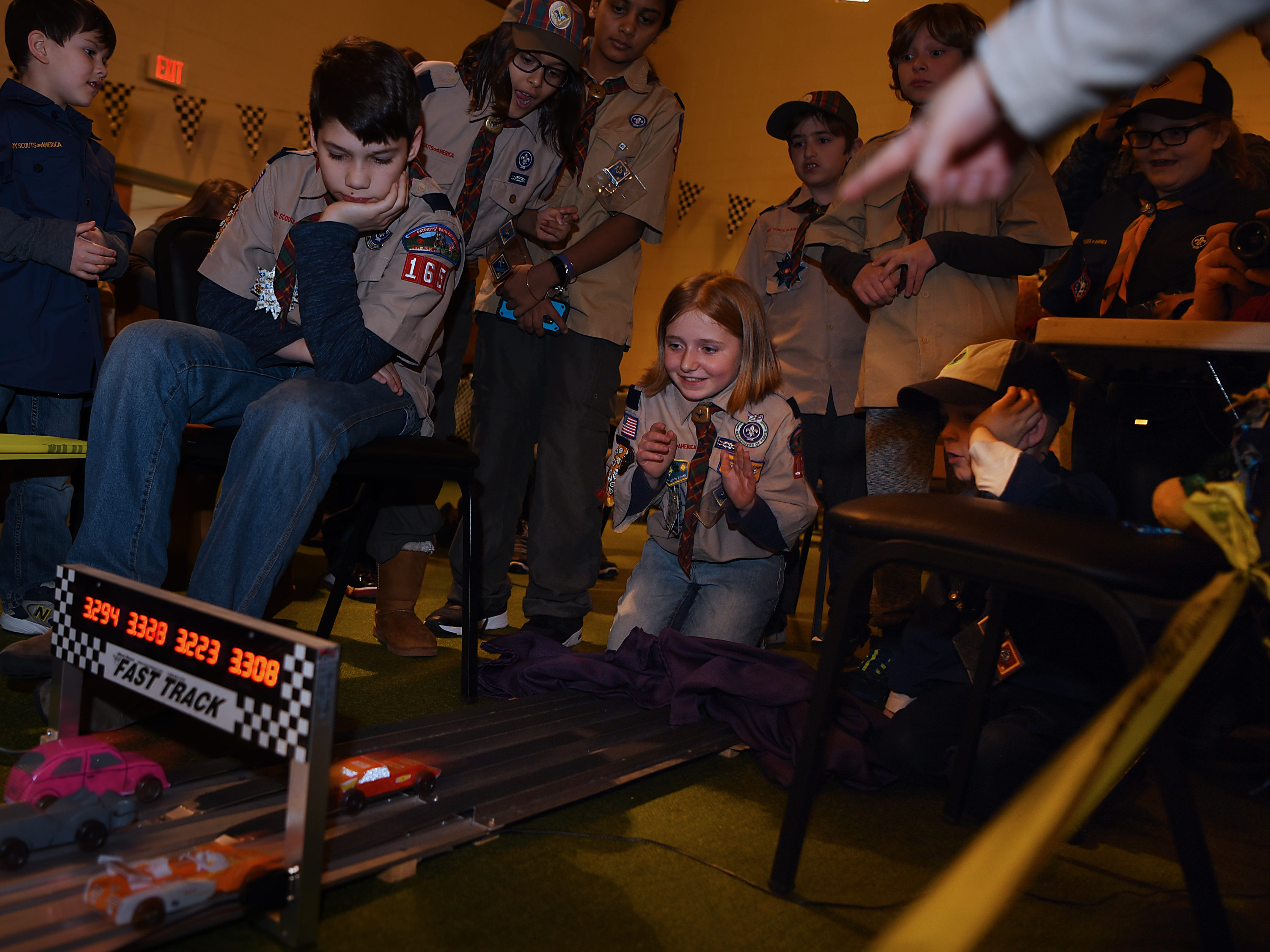 The Morris County Pinewood Derby at Holy Trinity Lutheran Church in Rockaway on Friday January 18, 2019. (Kneeling center) Madison Sipple, 10 years old with Cub Scout pack 165 Arrow of Light den, watches as the cars race to the finish line.