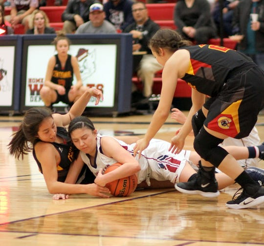 Senior wing Adriana Giron (white) went to the floor to save a Lady 'Cat possession on a loose ball.