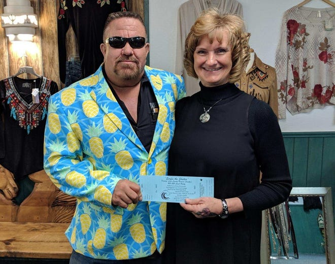 """Dressed for """"Surfin' the Shelter,""""Busy Bee Septic owner Bill Dupree purchasedthe first ticket to the Humane Society's 11th annual $10,000 cash party from former board member Shannon Bennett at Circle S Western Emporium.Tickets, still at $125 per couple, are available for the March 9 event at the Deming-Luna County Chamber of Commerce, Circle S, Deming Animal Clinic, Deming Animal Shelter, Dunne's Automotive, La Fonda Restaurant, Mimbres Valley Feed, Silver Whiskers Thrift Shop and from Humane Society board members. One lucky winner will go home from the cash party $10,000 richer. The event will be from 5:30 to 11 p.m. at the Mimbres Valley Special Events Center, 2300 E. Pine St. The evening will include, dinner, dancing a silent auction and spirits."""