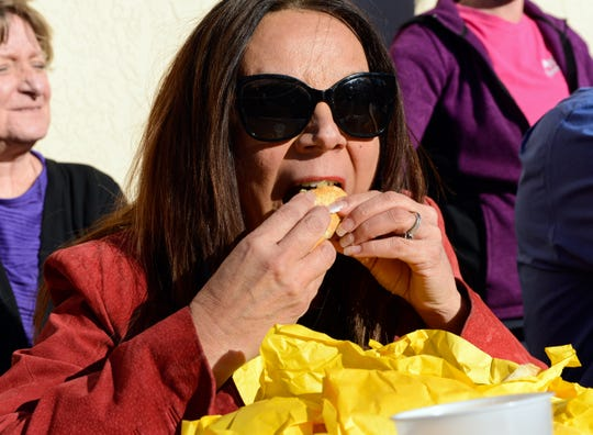 "Las Cruces City Councilor Kasandra Gandara stuffs a hamburger into her mouth during a hamburger-eating contest at Day's Hamburgers on Wednesday, Jan. 23, as part of the ""Construction Compadres"" program, created by three local chambers of commerce to draw attention to local businesses hurt by road construction projects."