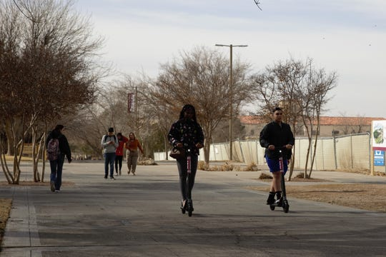 Students ride on Spin scooters on a walkway near Corbett Center on the New Mexico State University campus, Friday, Jan. 18, 2019.