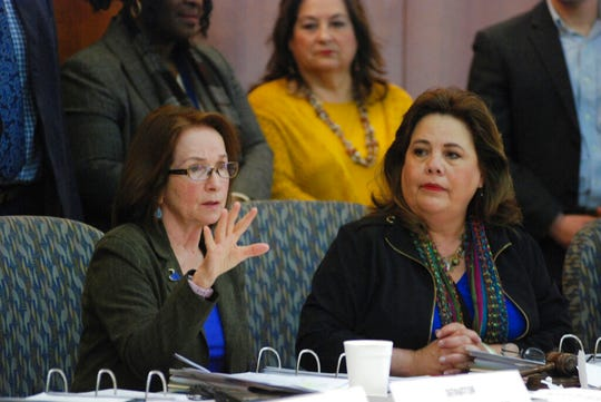 In this Jan. 14, 2019, file photo, state Sen. Mimi Stewart, D-Albuquerque, left, and Rep. Patria Lundstrom, D-Gallup, right, discuss the state's budget surplus in Santa Fe, N.M. A key New Mexico Legislative committee voted unanimously Wednesday, Jan. 23, 2019, to approve a proposal by Stewart that would incrementally increase minimum salaries for the state's public teachers and principals.