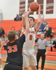 Northville's Zach Shoemaker (0) puts up a jumper over Brighton defender Shane Armstrong (33).