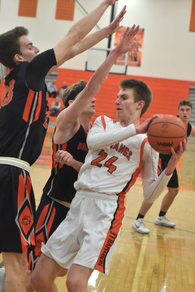 Mustang Steven Morrissey, right, finds his way to the basket blocked by a duo of Bulldogs during the teams' Jan. 22 match at Northville High.