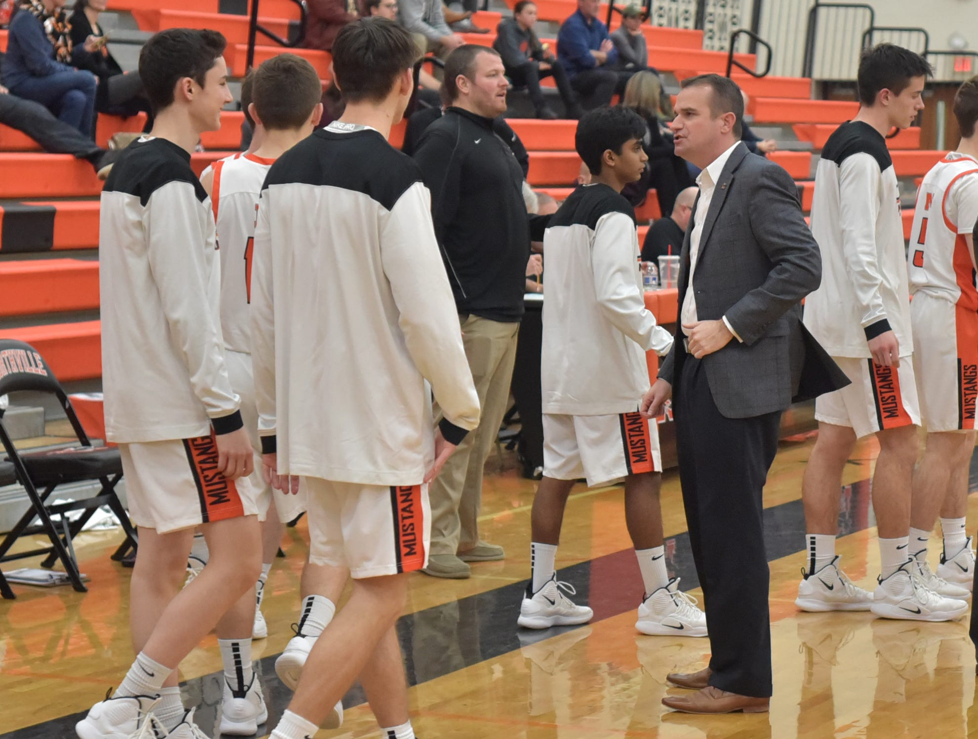 Northville Mustang coach Todd Sander, right, talks to his troops during a timeout in Tuesday night's game.