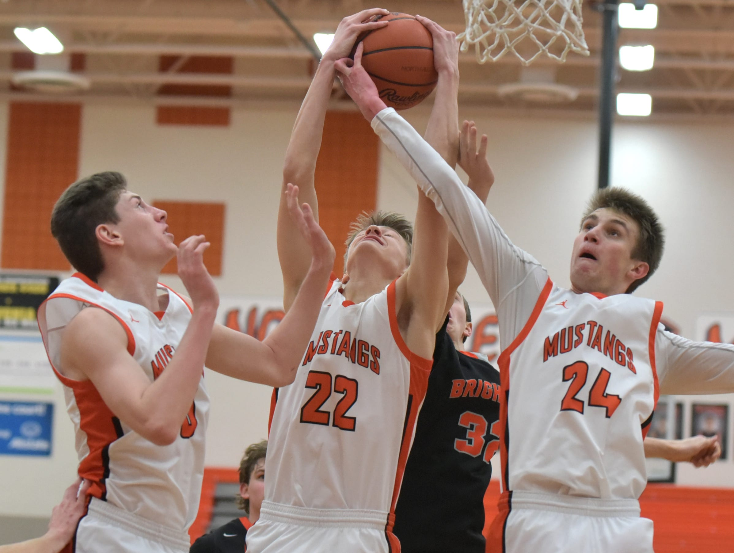 Three Northville Mustangs go up for a rebound including, from left, Zach Shoemaker, Ryan Pumper, and Steven Morrissey. Brighton Bulldog Owen Ehman, rear, is left grabbing at air.
