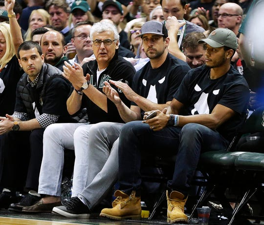 Packers quarterback Aaron Rodgers sits with Milwaukee Bucks owner Mark Lasry during a Bucks playoff victory over the Toronto Raptors in 2017. Rodgers has a 1 percent ownership stake in the  franchise.