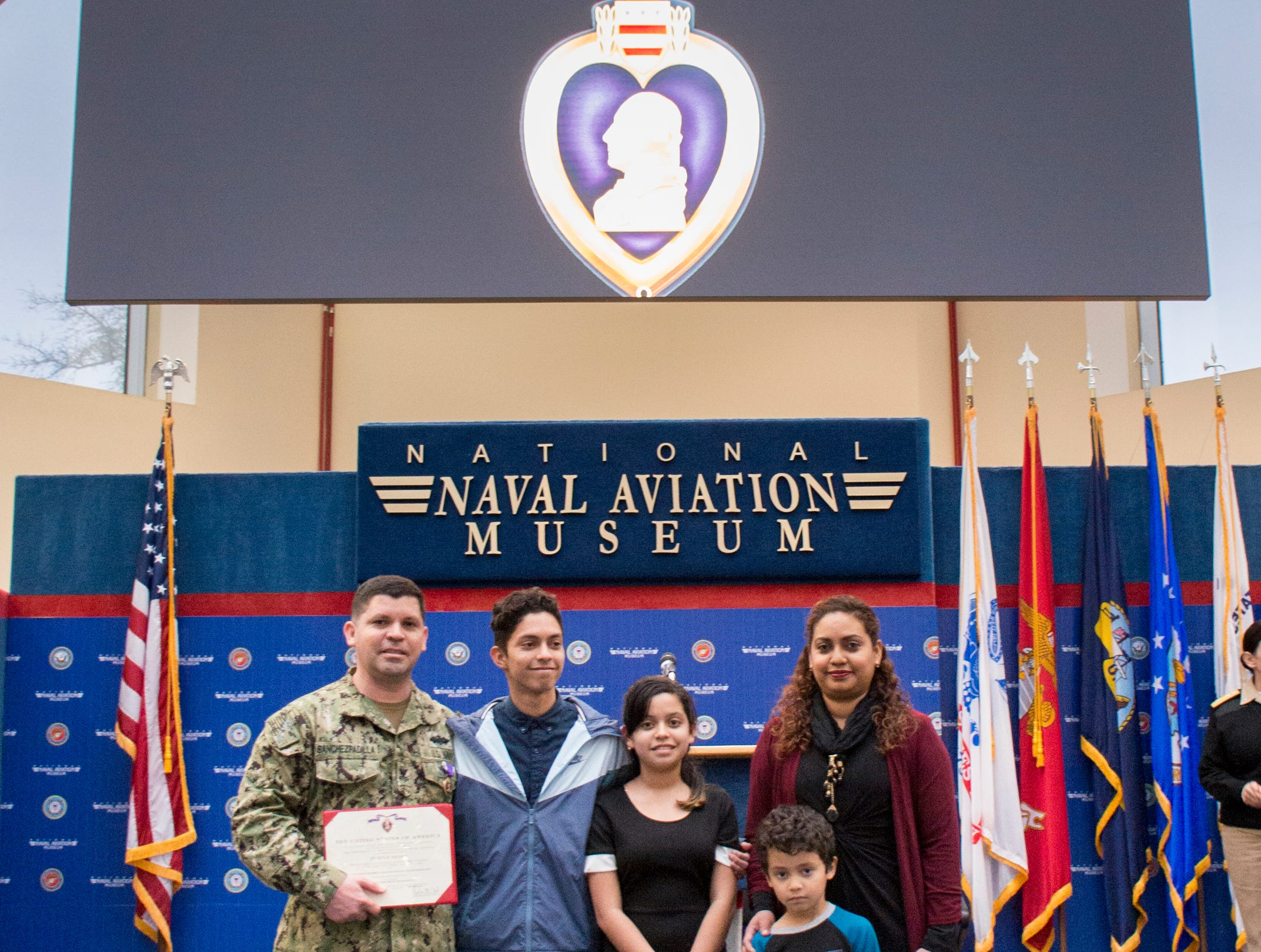 Navy Hospital Corpsman 1st Class Eduardo Sanchez-Padilla, left, poses with his family after  being awarded the Purple Heart during a ceremony at the National Naval Aviation Museum in Pensacola on Wednesday, January 23, 2019.  Sanchez-Padilla was wounded in Afghanistan in 2009.