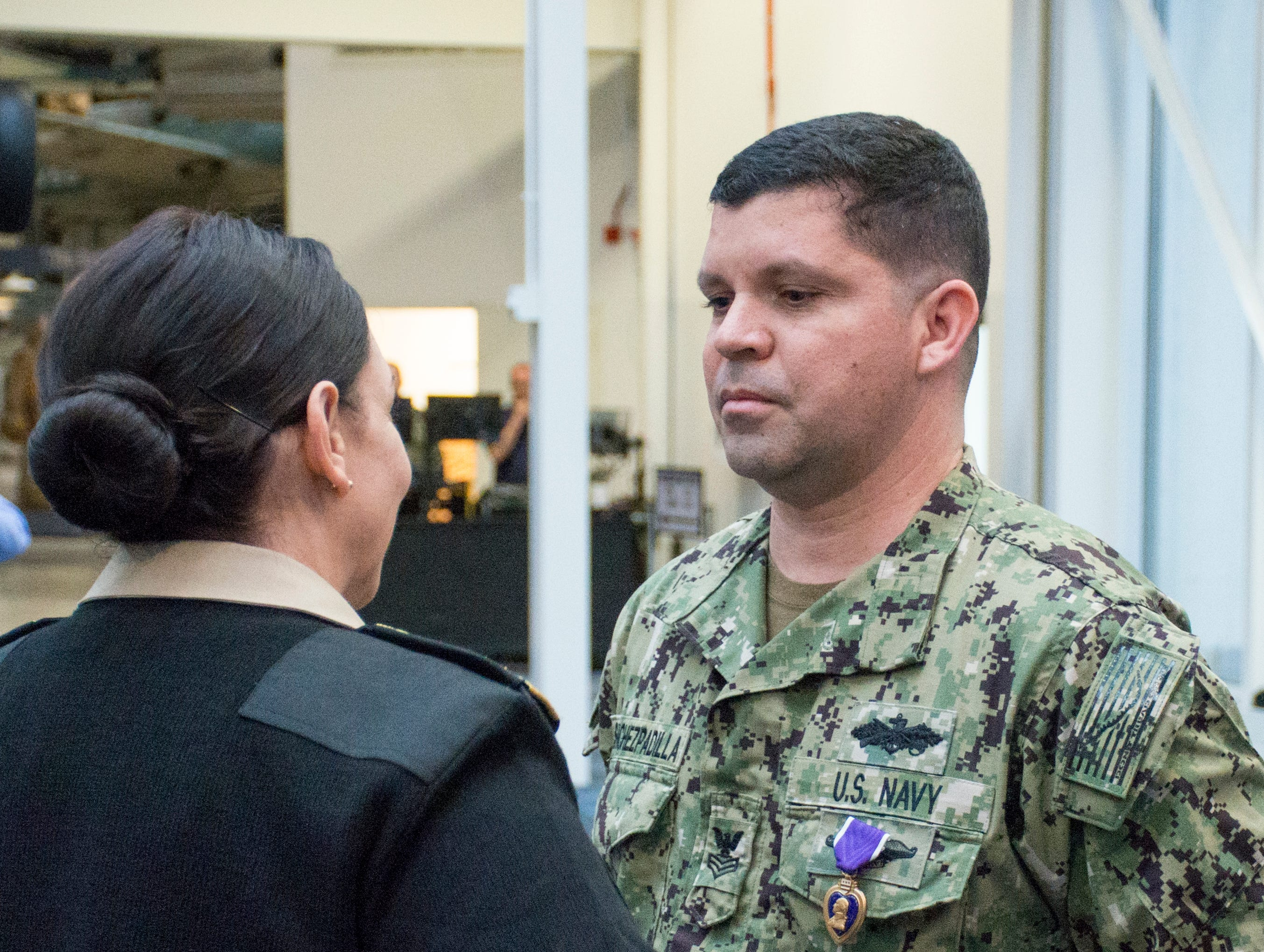 Rear Adm. Tina Davidson, left, presents Navy Hospital Corpsman 1st Class Eduardo Sanchez-Padilla the Purple Heart during a ceremony at the National Naval Aviation Museum in Pensacola on Wednesday, January 23, 2019.  Sanchez-Padilla was wounded in Afghanistan in 2009.