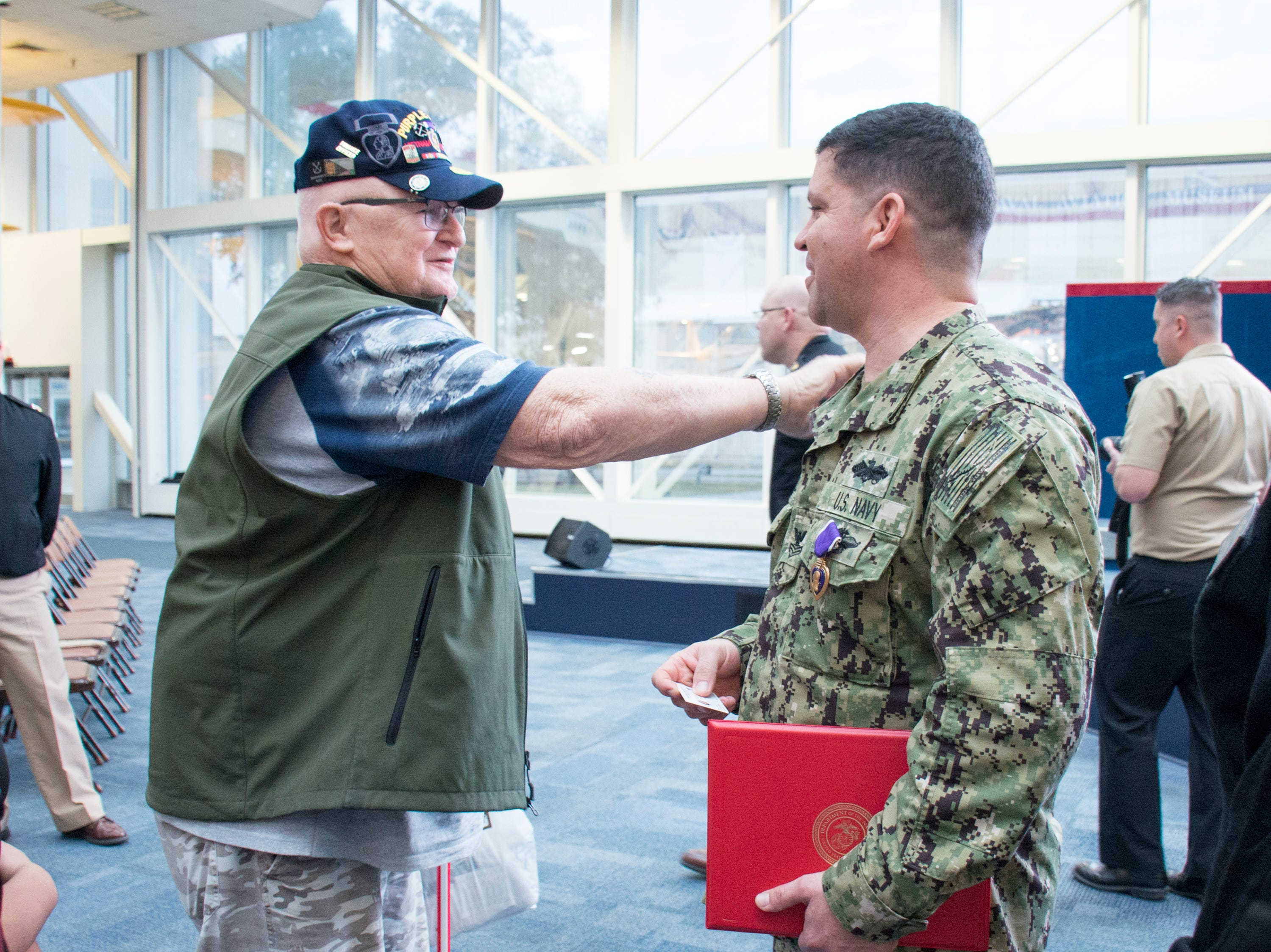Fellow Purple Heart recipient and Navy veteran Dale Prescott, left, greets Navy Hospital Corpsman 1st Class Eduardo Sanchez-Padilla after he was awarded the Purple Heart during a ceremony at the National Naval Aviation Museum in Pensacola on Wednesday, January 23, 2019.  Sanchez-Padilla was wounded in Afghanistan in 2009.  Prescott was injured in 1967.