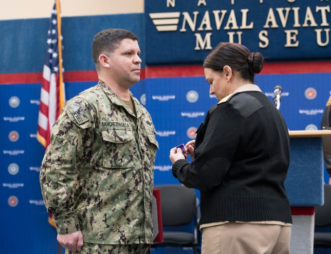 Rear Adm. Tina Davidson, right, presents Navy Hospital Corpsman 1st Class Eduardo Sanchez-Padilla the Purple Heart during a ceremony at the National Naval Aviation Museum in Pensacola on Wednesday, January 23, 2019.  Sanchez-Padilla was wounded in Afghanistan in 2009.