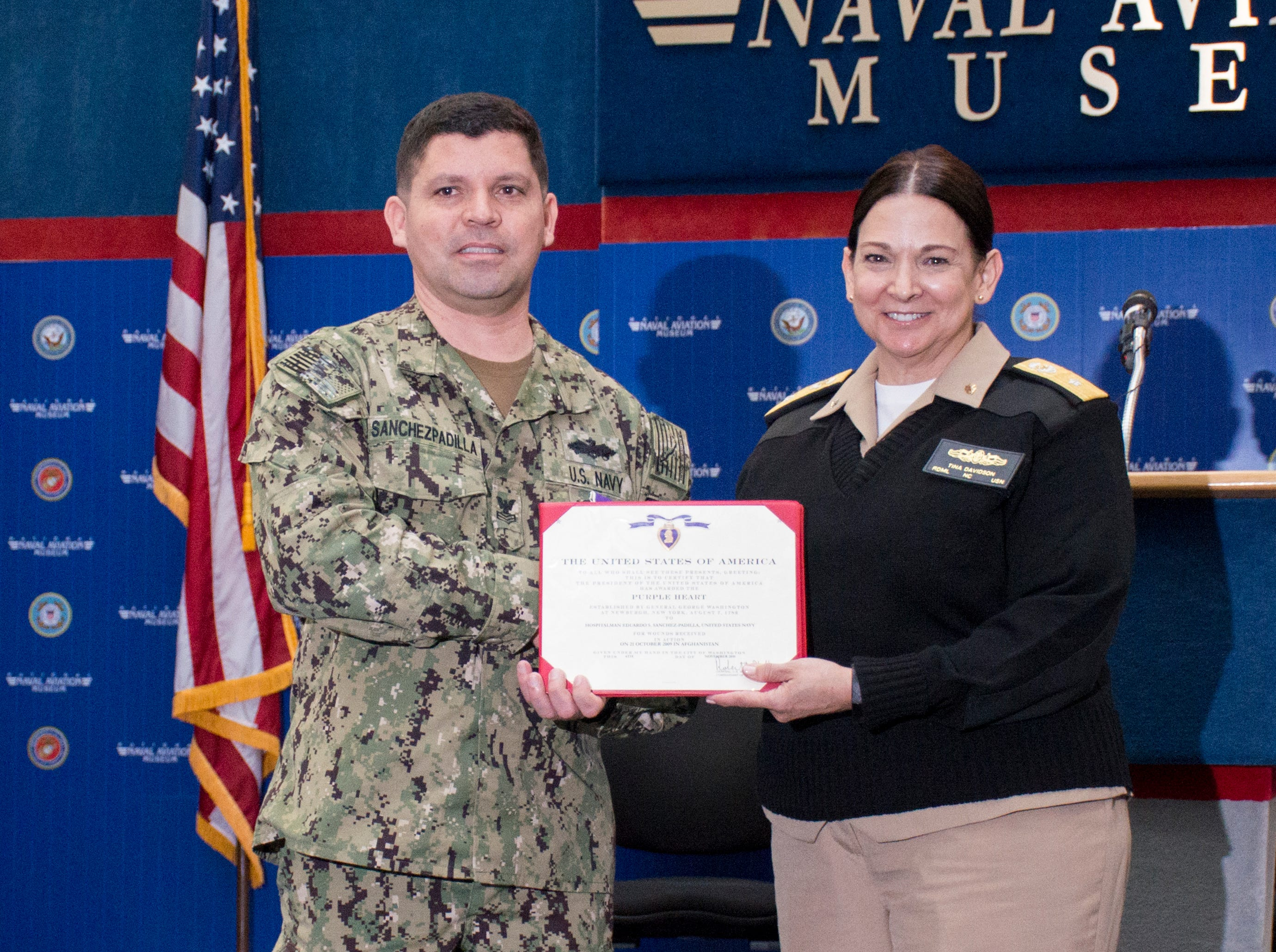 Rear Adm. Tina Davidson, right, poses with Navy Hospital Corpsman 1st Class Eduardo Sanchez-Padilla after presenting him the Purple Heart during a ceremony at the National Naval Aviation Museum in Pensacola on Wednesday, January 23, 2019.  Sanchez-Padilla was wounded in Afghanistan in 2009.