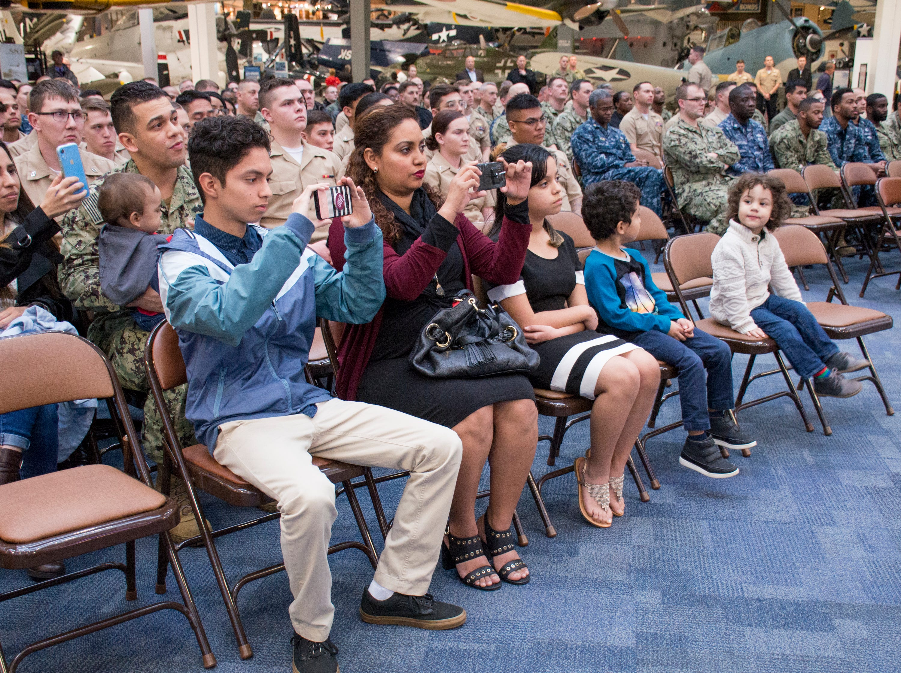 Navy Hospital Corpsman 1st Class Eduardo Sanchez-Padilla's family record video as he is awarded the Purple Heart during a ceremony at the National Naval Aviation Museum in Pensacola on Wednesday, January 23, 2019.  Sanchez-Padilla was wounded in Afghanistan in 2009.