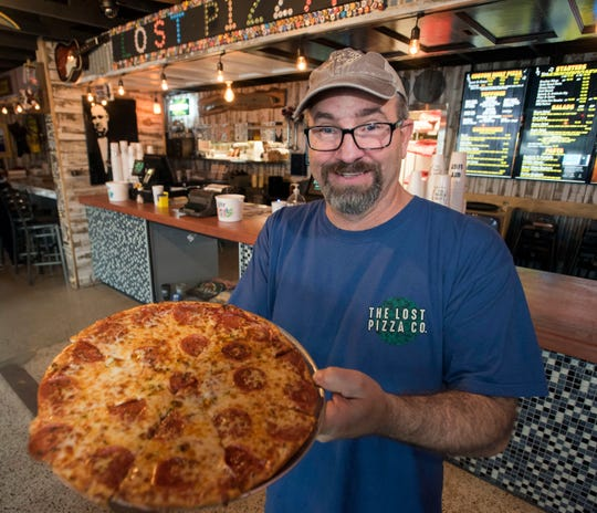 Bruce Quinton, the owner of Lost Pizza Co. in Pensacola, shows off one of his restaurant's signature pies on Wednesday, Jan. 23, 2019.