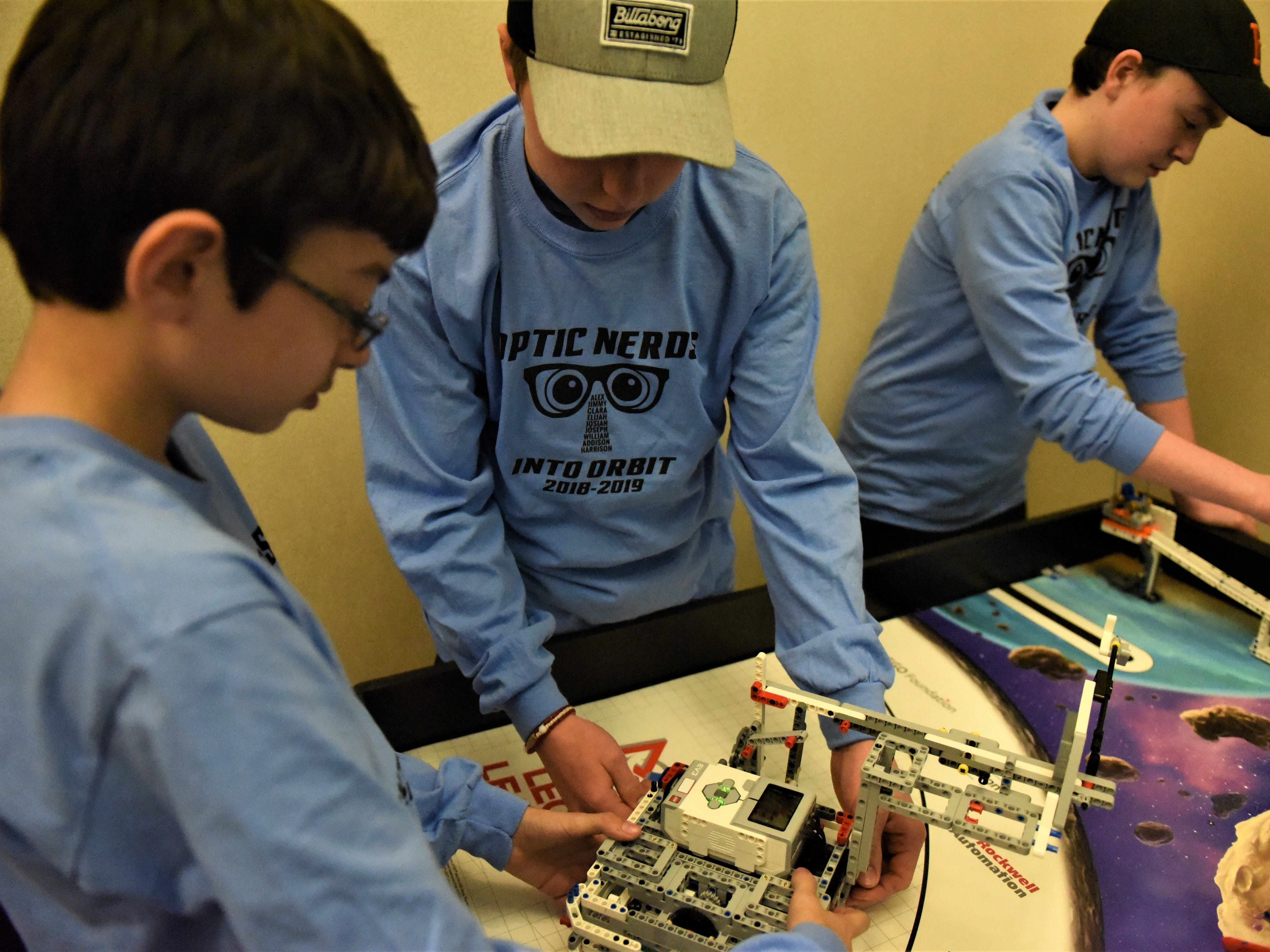 From left, Jimmy Himmerlein, 13, Elijah Morton, 13, and Josiah Brower, 13, adjust their robot for an upcoming robotics competition at the Penn State Berks campus on Jan 26.