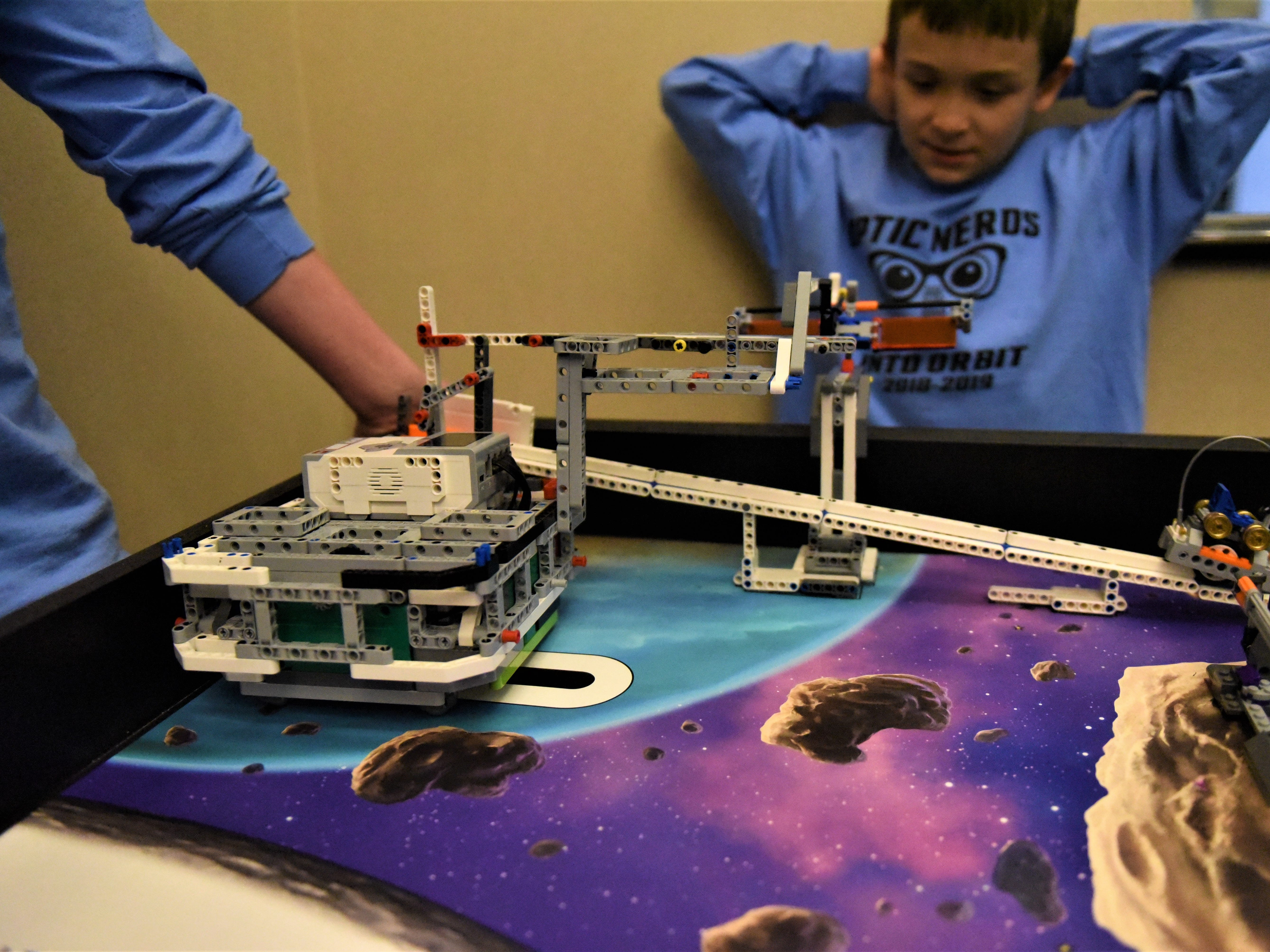 Harrison Roth, 9, watches as the robot completes a task. The Optic Nerds team name is a play on words, stemming from optic nerves. The theme of the robotics competition is Into Orbit, and astronauts often develop vision problems in space because their optive nerves swell andwarp.