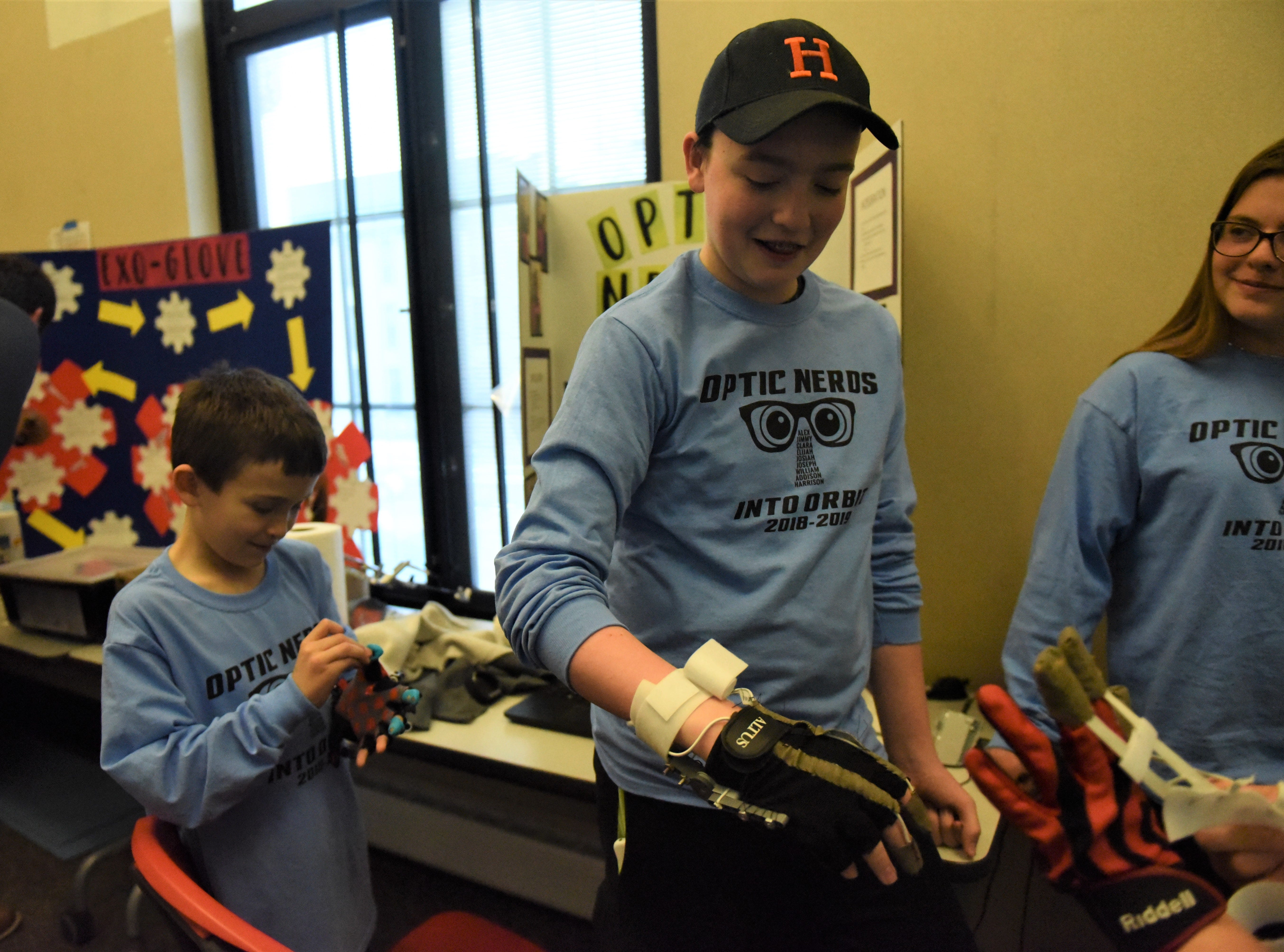 From left, Harrison Roth, 9, Josiah Brower, 13 and Clara Morton, 15, test the exo-skeleton glove Clara and Josiah designed that would help astronauts' motor function in outer space. The two got the idea for this invention after they went on a field trip to George Washington University where they got to interview Dr. Serena Auñon-Chancellor, a woman currently living in space.
