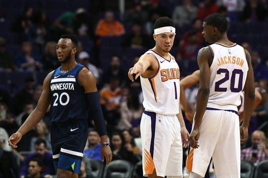Jan 22, 2019; Phoenix, AZ, USA; Phoenix Suns guard Devin Booker (1) and forward Josh Jackson (20) talk on the court against the Minnesota Timberwolves at Talking Stick Resort Arena. Mandatory Credit: Jennifer Stewart-USA TODAY Sports