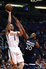 Suns guard Devin Booker shoots over Timberwolves guard Josh Okogie during the first half of a game Jan. 22.