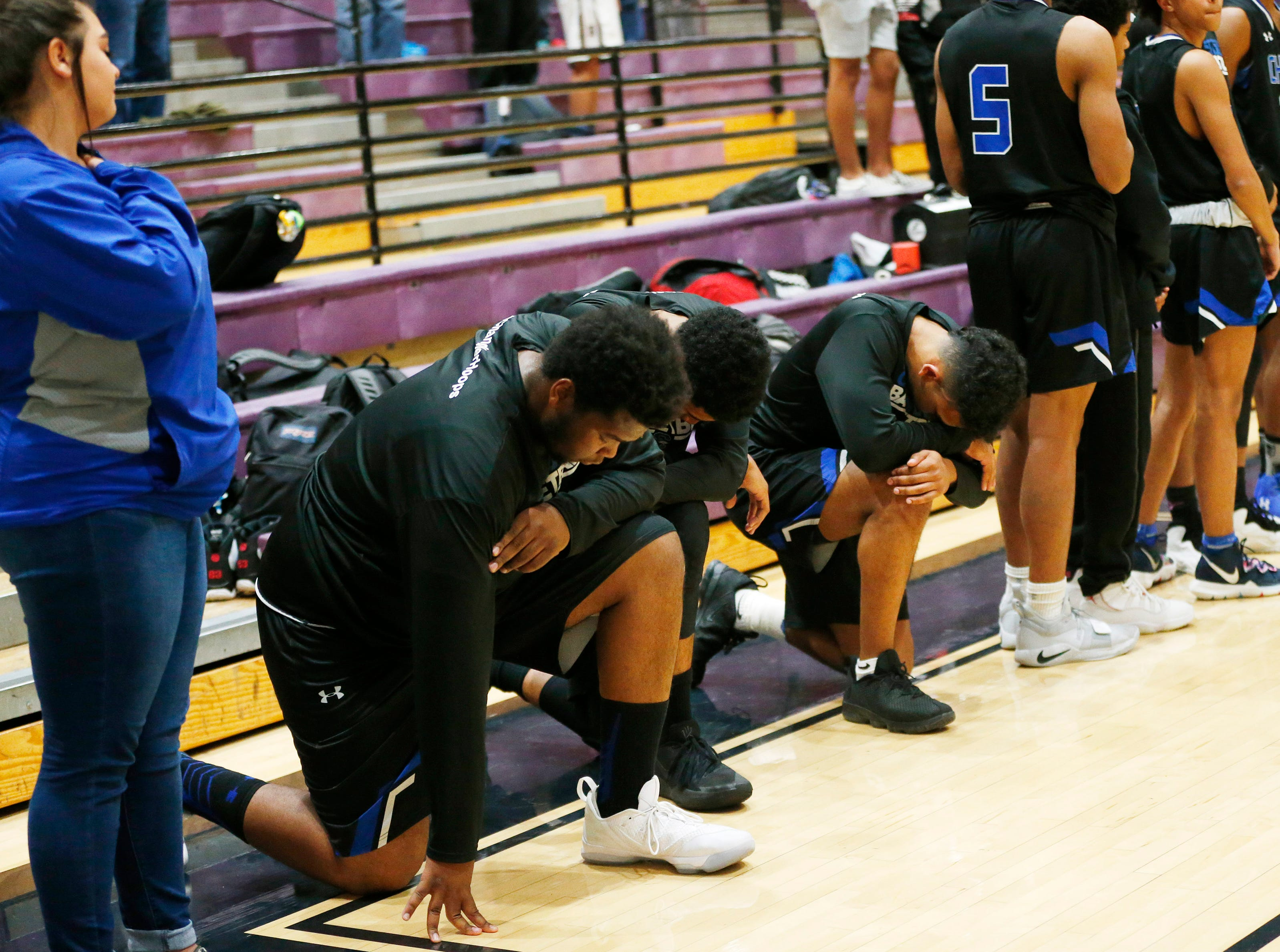 Chandler High basketball player take a knee during the National Anthem before playing against Hamilton in Chandler, Ariz. January 22, 2019.