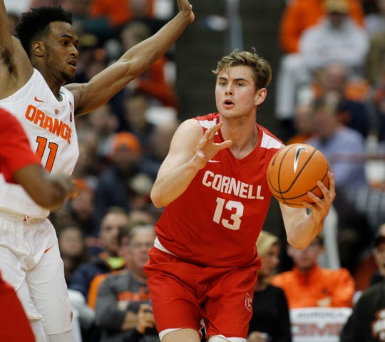Cornell's Stone Gettings, right, looks to pass the ball under pressure from Syracuse's Oshae Brissett, left, in the second half of an NCAA college basketball game in Syracuse, N.Y., Friday, Nov. 10, 2017. (AP Photo/Nick Lisi)