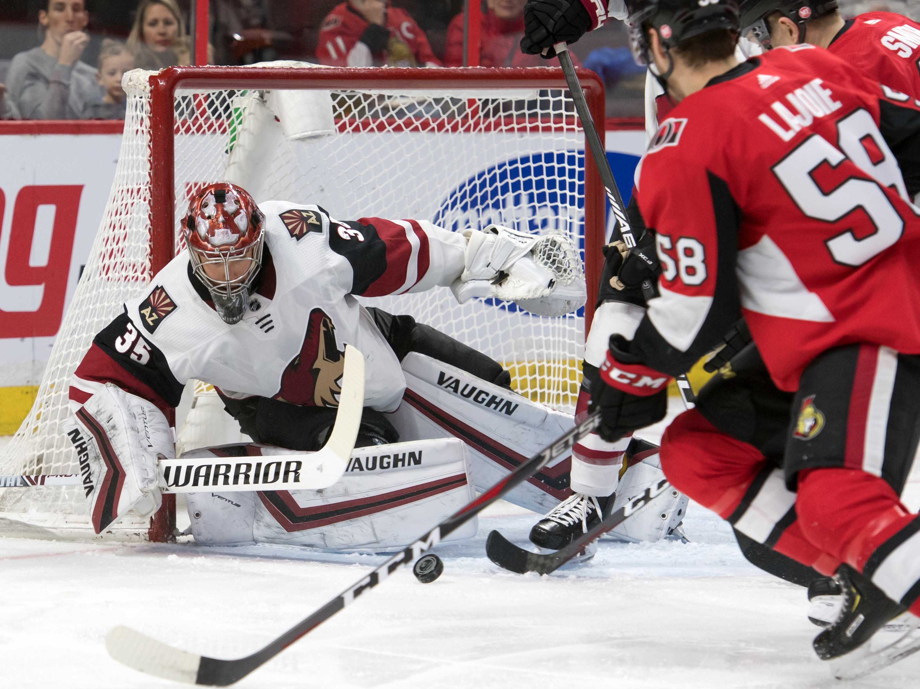 Jan 22, 2019; Ottawa, Ontario, CAN; Arizona Coyotes goalie Darcy Kuemper (35) makes a save in front of  Ottawa Senators defenseman Maxime Lajoie (58) in the second period at the Canadian Tire Centre. Mandatory Credit: Marc DesRosiers-USA TODAY Sports
