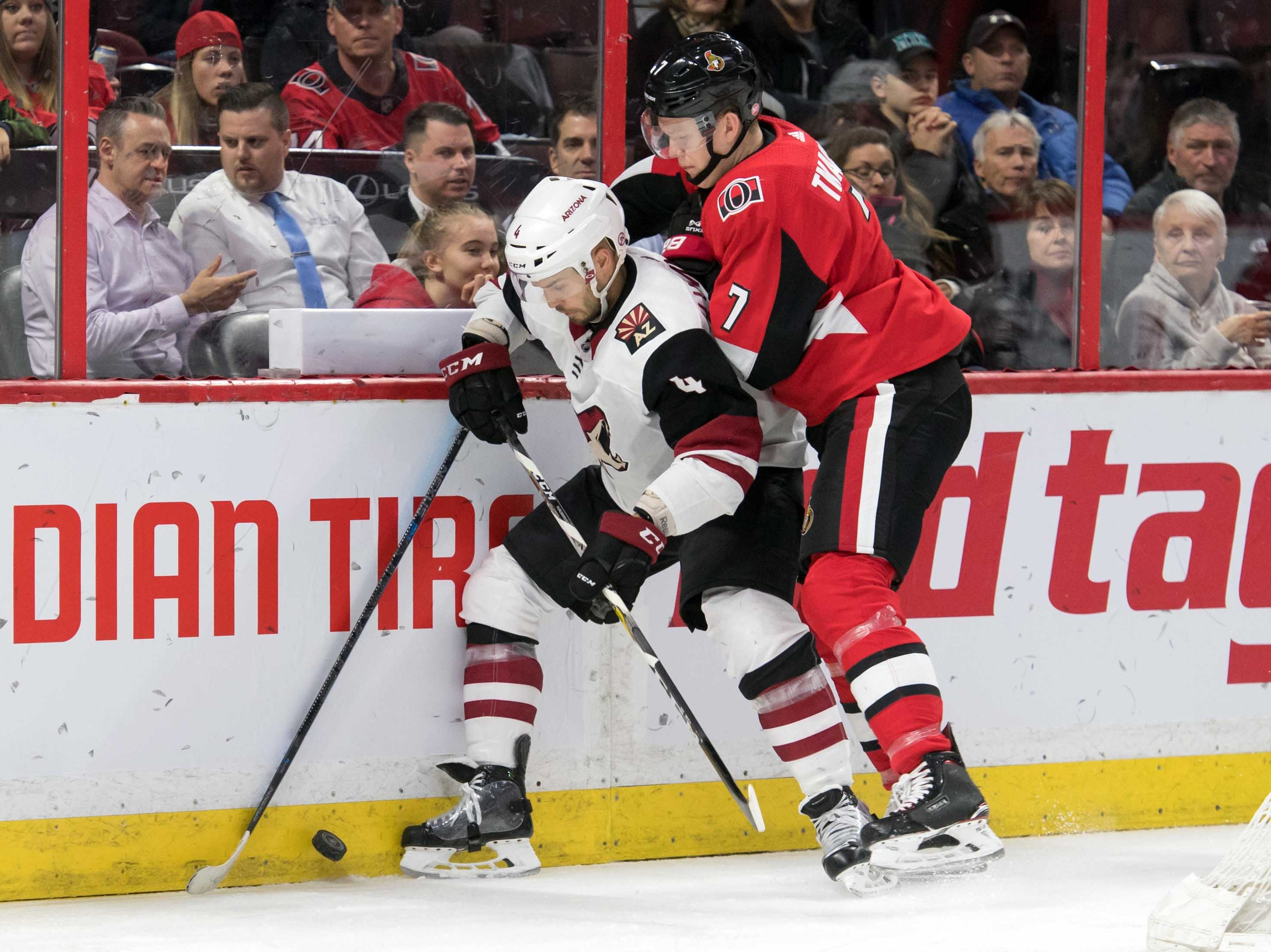 Jan 22, 2019; Ottawa, Ontario, CAN; Arizona Coyotes defenseman Niklas Hjalmarsson (4) and  Ottawa Senators left wing Brady Tkatchuk (7) battle for the puck in the second period at the Canadian Tire Centre. Mandatory Credit: Marc DesRosiers-USA TODAY Sports