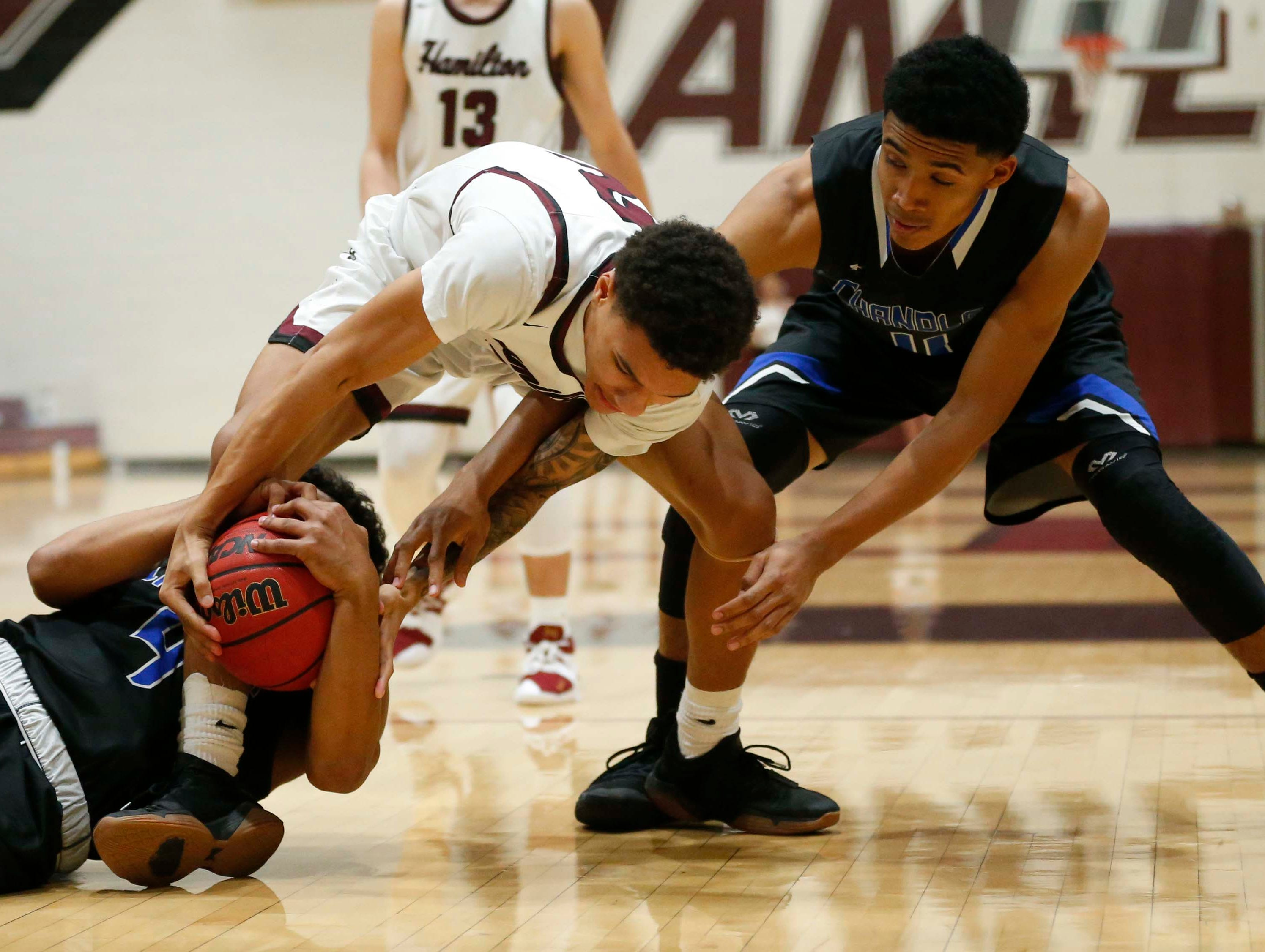 Hamilton's Malik Whitaker (2) battles with Chandler's Adrian Chandler (left) and Isaiah Somers (11) for the ball during the first half in Chandler, Ariz. January 22, 2019.