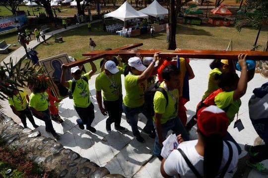 Feligreses cargan una cruz de madera gigante y una imagen de Jesús, en Panamá.