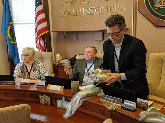 Sandusky County Commissioners Kay Reiter, left, Russ Zimmerman, middle and Scott Miller, right, review water and filter samples provided by Ream Road resident Lonnie Burke.