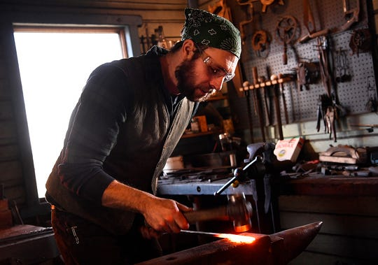 Derick Kemper of Damselfly Forge in Fawn Grove hammers out heated steel into the shape of a knife blade. Wednesday, January 23, 2019. 