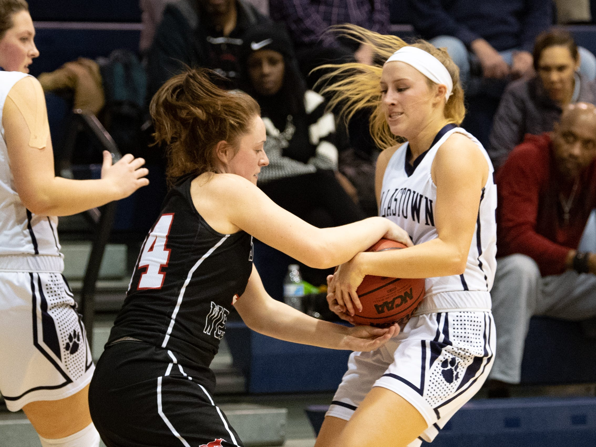 Maddy McMaster (34) of South Western and Lily Jamison (20) of Dallastown wrestle for the ball during the YAIAA girls' basketball game, Tuesday, January 22, 2019. The Wildcats defeated the Mustangs 38-35.
